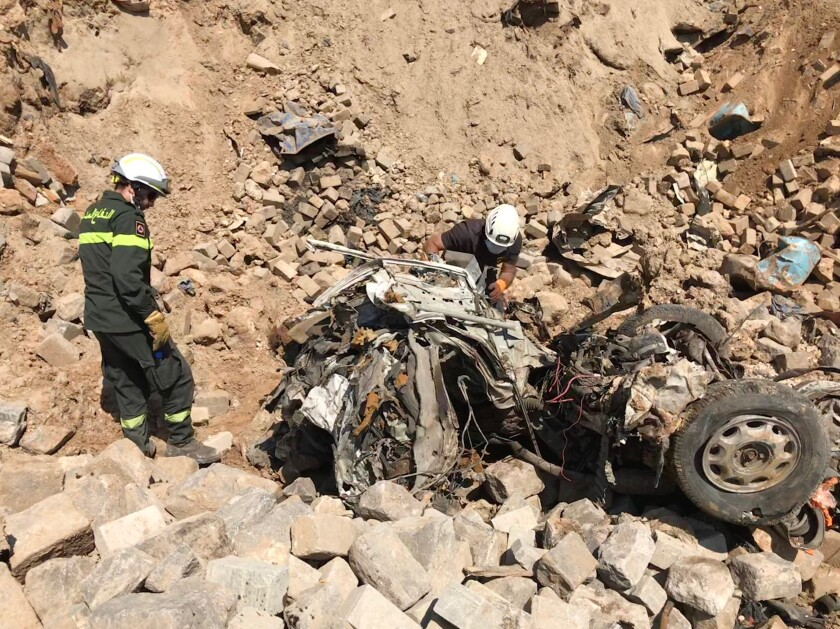 Lebanese civil defense workers search for the bodies of those killed in the explosion at Beirut's port.