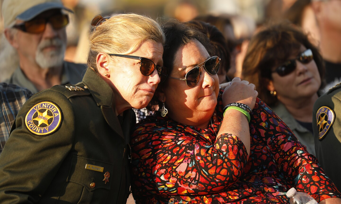 """THOUSAND OAKS, CA - NOVEMBER 7, 2019 Ventura County Undersheriff Monica McGrath, left, comforts Karen Helus wife of Ventura County Sheriff Sgt Ron Helus who was killed in the Borderline mass shooting during the dedication services at the Healing Garden constructed at Conejo Creek North Park in Thousand Oaks to remember the 12 lives taken and the 248 that survived the Borderline Bar and Grill mass shooting on the one-year anniversary of the mass shooting. Brandon was best friends with victim Cody Coffman and """"like a brother since they were 7 years old."""" (Al Seib / Los Angeles Times)"""