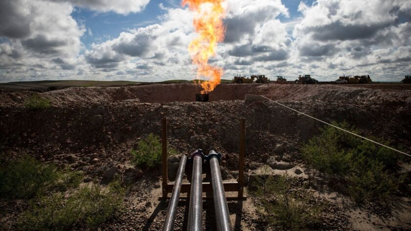 With oil prices and production surging and regional gas prices in a tailspin, Texas is considering whether to loosen its restrictions on burning off excess gas that is pumped up with oil.