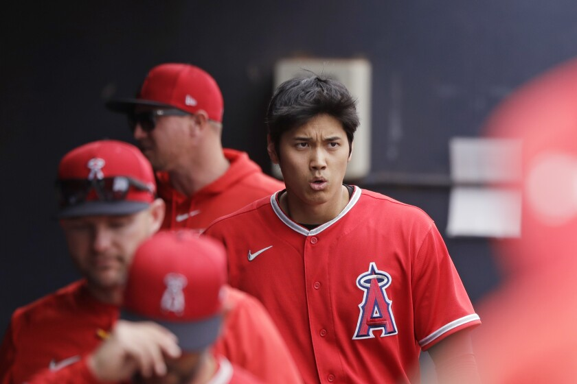 Shohei Ohtani walks in the dugout after grounding out during a spring training game against the Mariners on March 10.