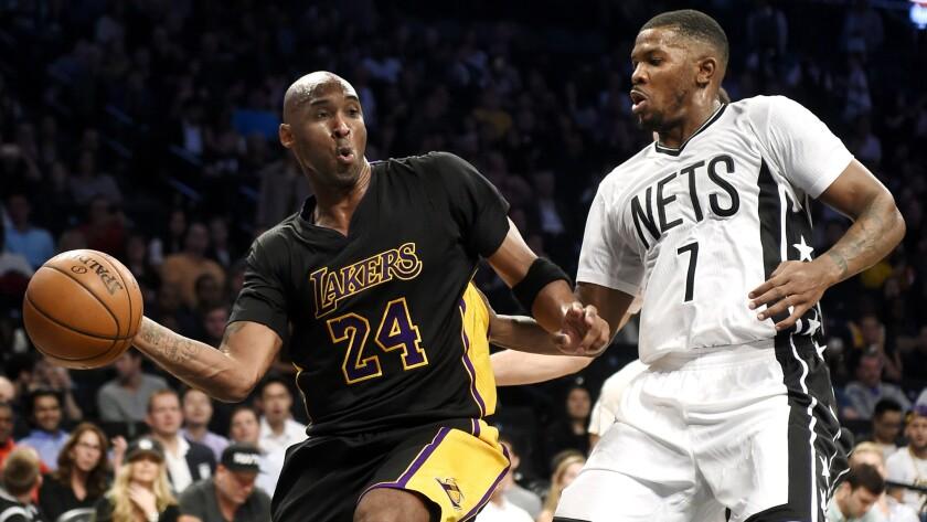 Lakers guard Kobe Bryant passes the ball around Nets forward Joe Johnson (7) during the first half of an NBA basketball game Friday, Nov. 6, 2015, in New York. (AP Photo/Kathy Kmonicek)