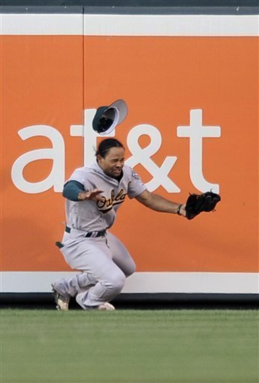Oakland Athletics center fielder Coco Crisp makes a leaping catch and hits the wall on a ball hit by Baltimore Orioles' Corey Patterson in the second inning of a baseball game Wednesday, June 30, 2010, in Baltimore. Catcher interference was called on the play. (AP Photo/Gail Burton).