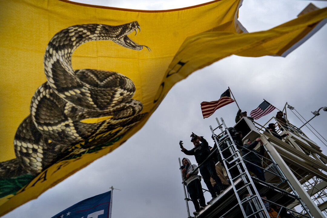 People gesture and wave flags atop scaffolding