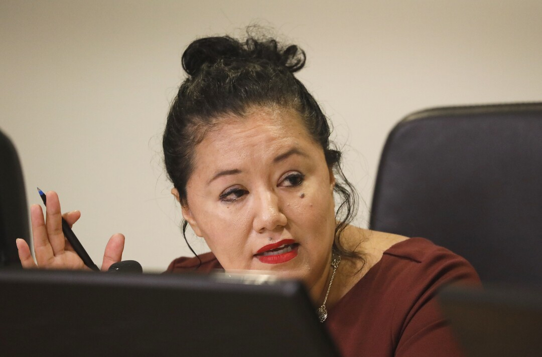 Delia Ibarra sits at a meeting table with a pen in her hand.