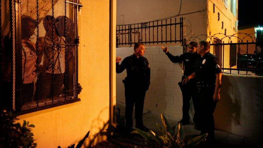 Sgt. Jeritt Severns, left, speaks with other LAPD officers about a shooting call in South L.A.