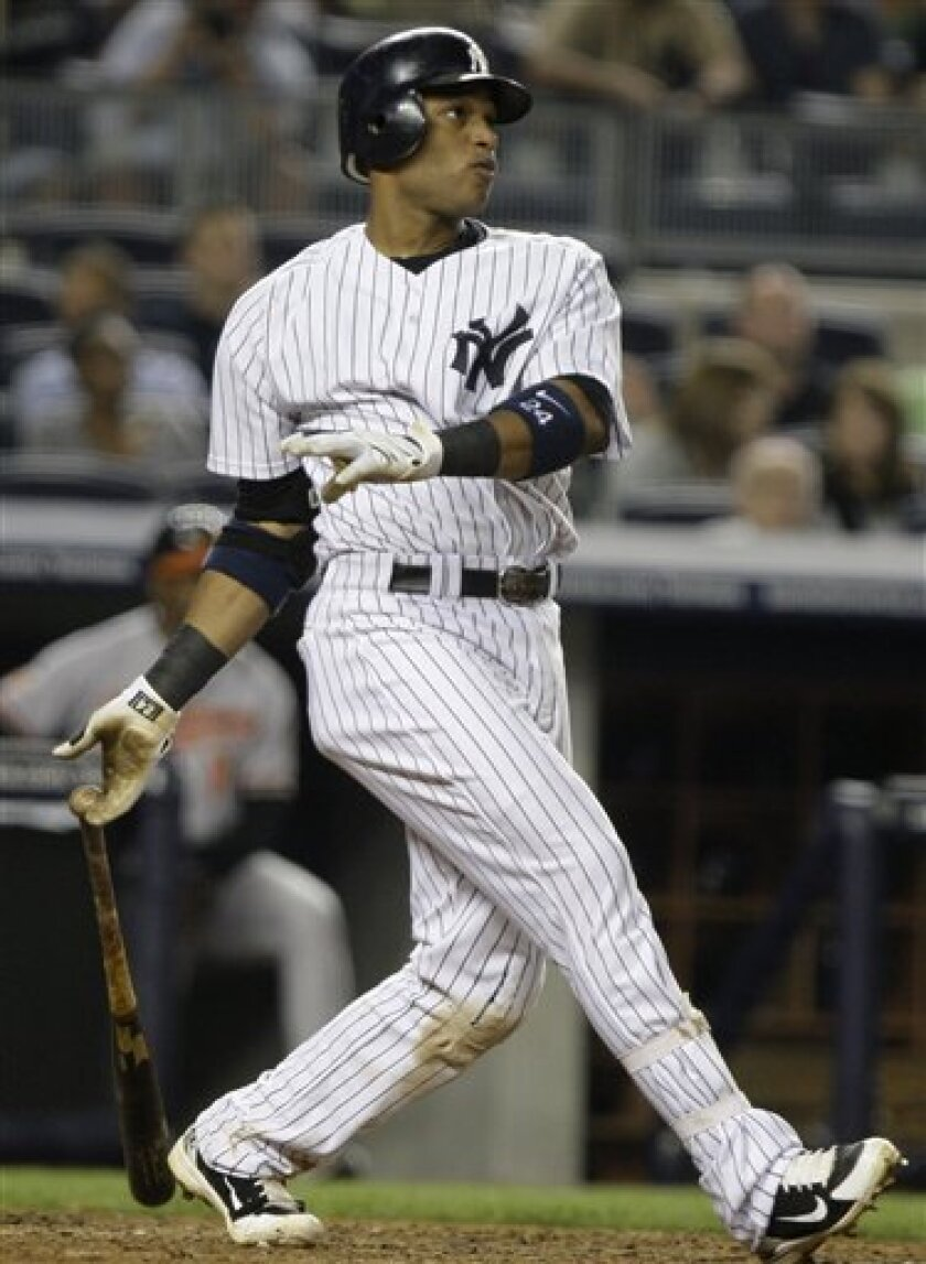 New York Yankees' Robinson Cano follows through on a two-run home run during the seventh inning of a baseball game against the Baltimore Orioles on Wednesday, June 2, 2010, in New York. (AP Photo/Frank Franklin II)