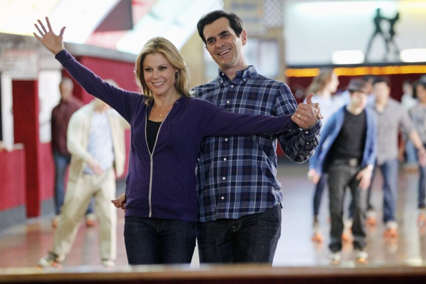 """This image released by ABC shows Julie Bowen, left, and Ty Burrell in a scene from """"Modern Family.""""  Qantas airline is partnering with the show's production company, 20th Century Fox, to fly the cast to Australia next month for a two week shoot of an upcoming vacation episode of the ABC comedy. The"""