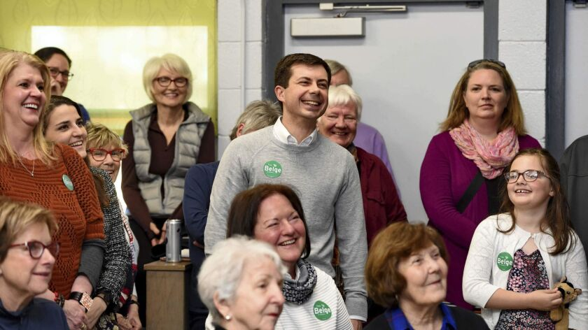 South Bend Mayor Pete Buttigieg, center, shares a laugh while he waits to speak to a crowd about his