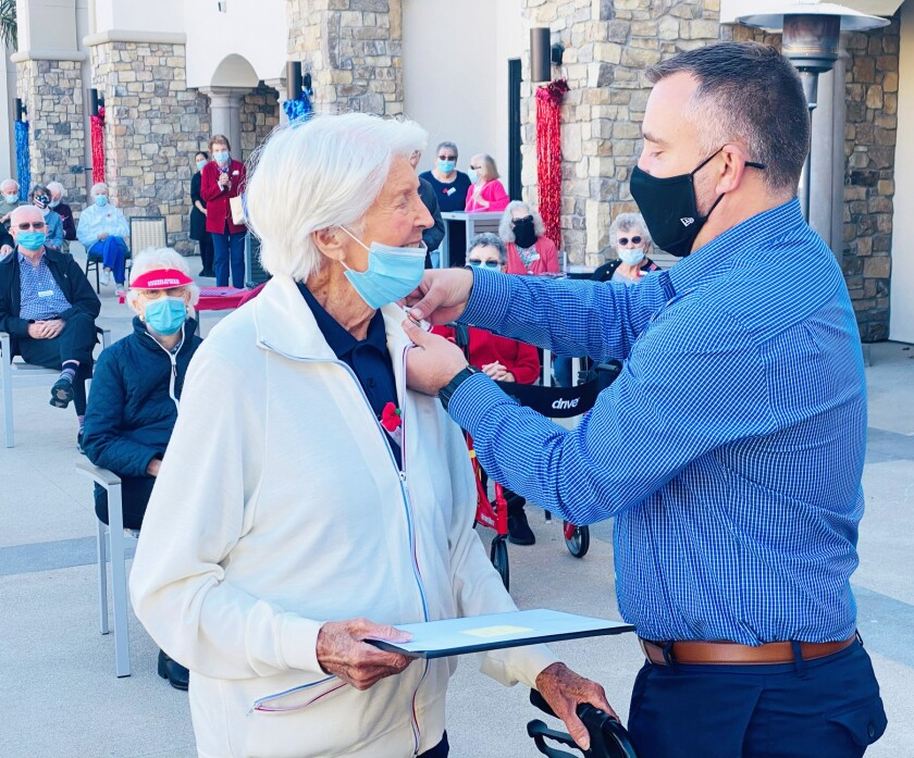 Silvergate resident Anna Palmer, who served as a Navy WAVE, receiving a commemoration pin from Derrik Staple.