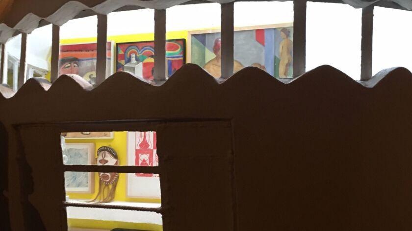 "The exhibition ""Fantasía"" as seen through the NuMu's windows at night."
