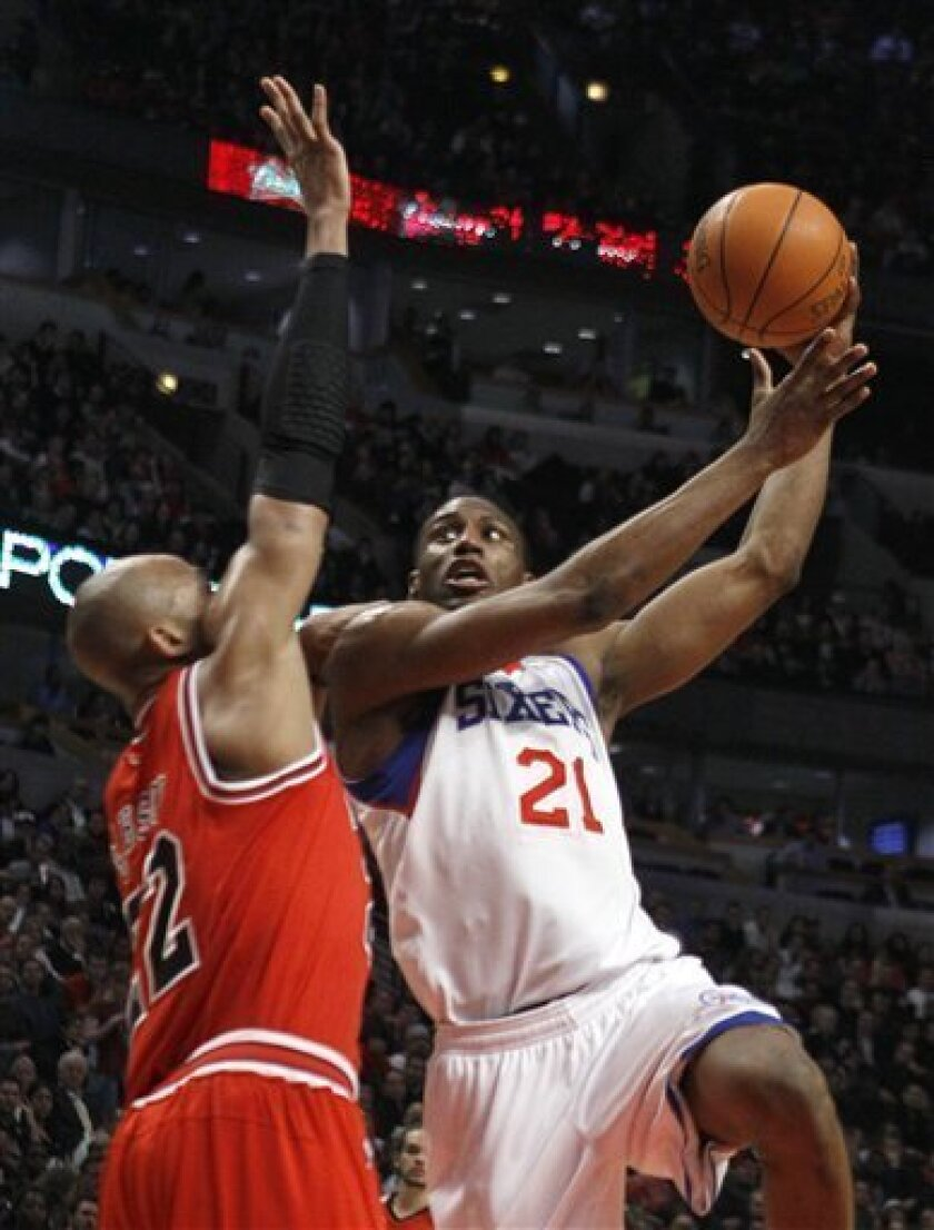 Philadelphia 76ers forward Thaddeus Young, right, shoots over Chicago Bulls forward Taj Gibson, during the first half of an NBA basketball game, Monday, March 28, 2011, in Chicago. (AP Photo/Charlie Arbogast)