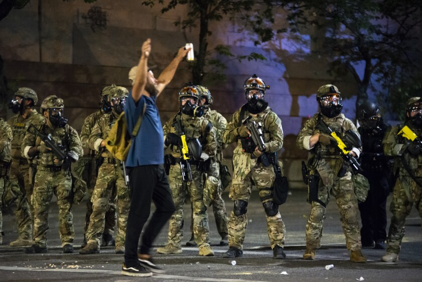 A protester holds his hands in the air while walking past a group of federal officers on July 21 in Portland, Ore.