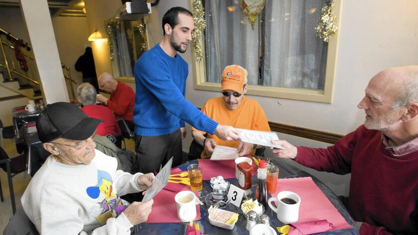 Keenan House resident Stephen Coppo (standing) takes breakfast orders from Raymond Knauss (left), Robert Michaels and Bruce Brown in December at the Allentown facility.