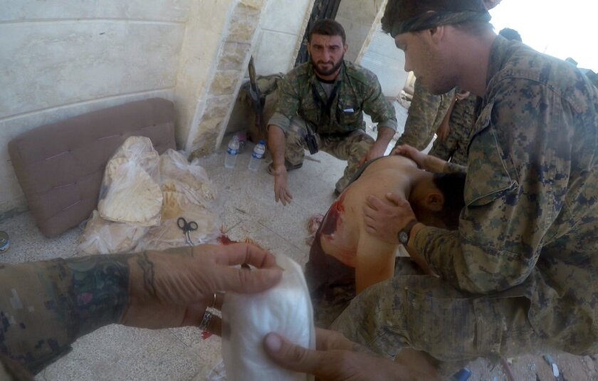 Shirley tends to a wounded man in Manbij, Syria.