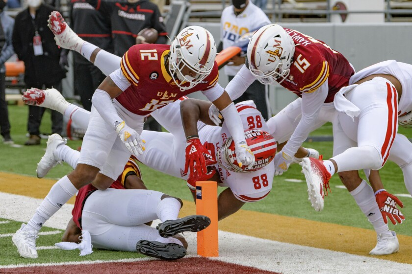 Louisiana-Lafayette tight end Johnny Lumpkin (88) is stopped short of a touchdown by Louisiana-Monroe cornerback Kenderick Marbles (12) and safety Austin Hawley (15) during the first half of an NCAA college football game in Monroe, La., Saturday, Nov. 28, 2020. (AP Photo/Matthew Hinton)