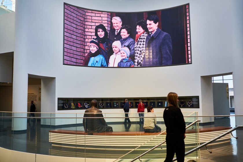 A bronze statue of Boris Yeltsin is mounted on a bench overlooking a photo of Yeltsin with his family in Boris Yeltsin Museum in Yekaterinburg.