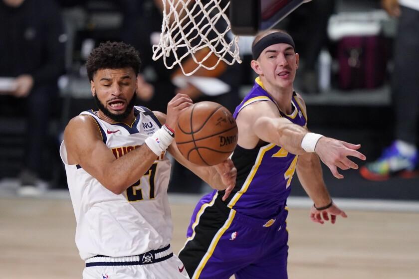 Lakers guard Alex Caruso blocks a layup by Nuggets star Jamal Murray.