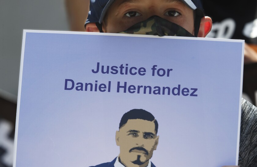 Matthew Hernandez, 8, holds a sign with a picture of his uncle, Daniel Hernandez, who was fatally shot by an LAPD officer.