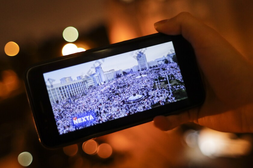 A man in Minsk, Belarus, looks at Telegram channel NEXTA Live on his smartphone.