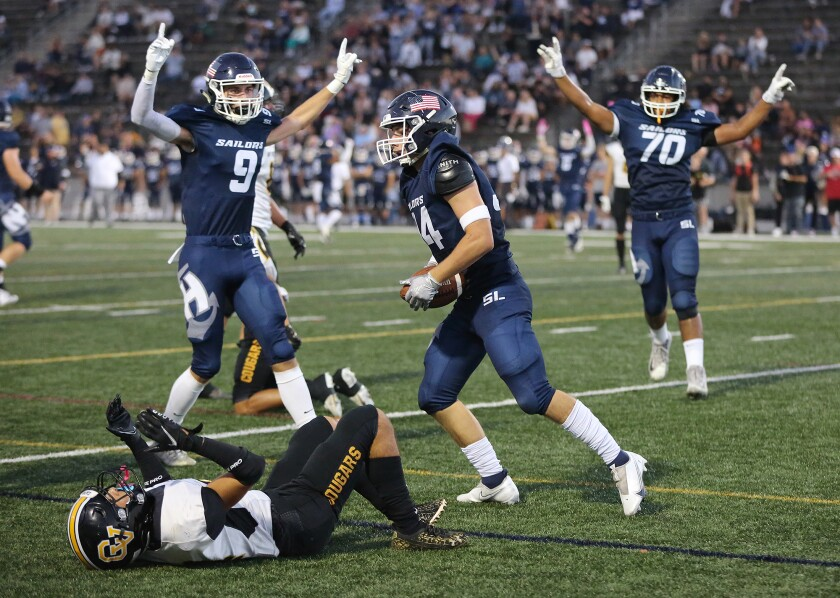 Newport Harbor's Payton Irving (34) reaches the end zone for a touchdown with Duke Starnes (9) and  Grayson Simon (70).
