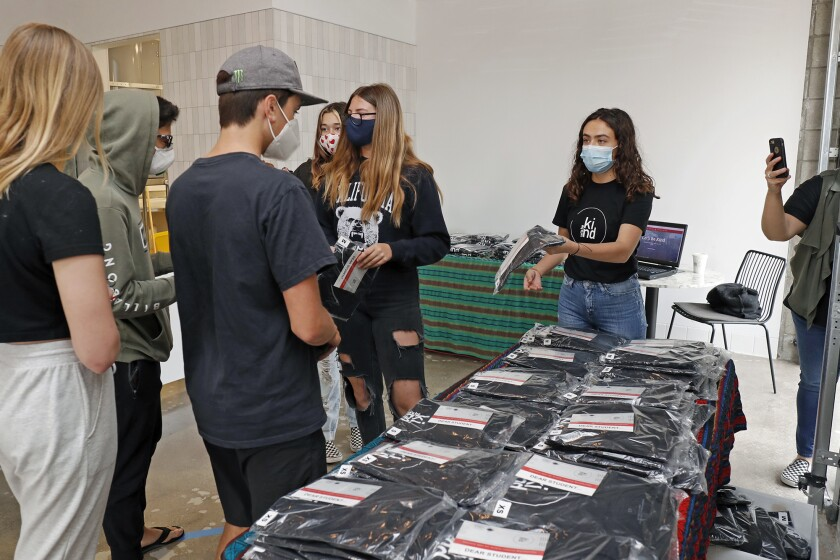 """Rebekah Robeck, right, a sophomore at Costa Mesa High School, hands out """"Let's Be Kind"""" T-shirts to a group of eighth-graders from Costa Mesa Middle School at Buenas Coffee on Friday."""