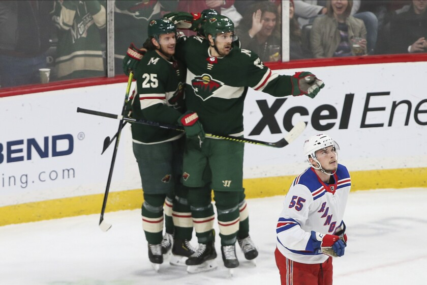 Minnesota Wild's Jonas Brodin,left, is congratulated by teammates after scoring against the New York Rangers during the first period of an NHL hockey game Thursday, Feb. 13, 2020, in St. Paul, Minn. Watching the scoreboard is Rangers' Ryan Lindgren. (AP Photo/Jim Mone)