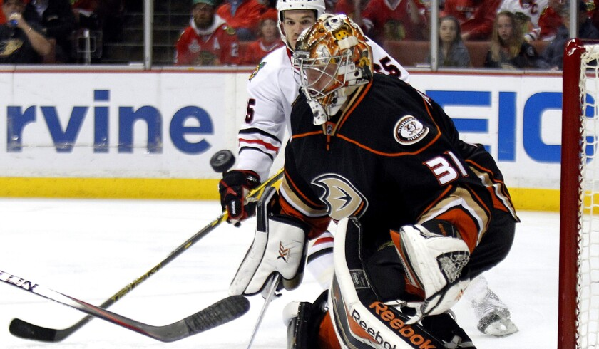 Ducks goalie Frederik Andersen looks to block a shot in the first period as Blackhawks center Andrew Shaw (65) skates into position for a rebound.