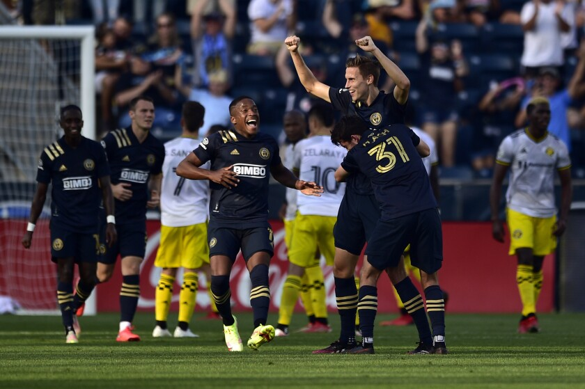 Philadelphia Union's Jack Elliott, second from right, receives a hug from Leon Flach (31) after scoring a goal against the Columbus Crew during the first half of an MLS soccer match, Sunday, Oct. 3, 2021, in Chester, Pa. (AP Photo/Derik Hamilton)