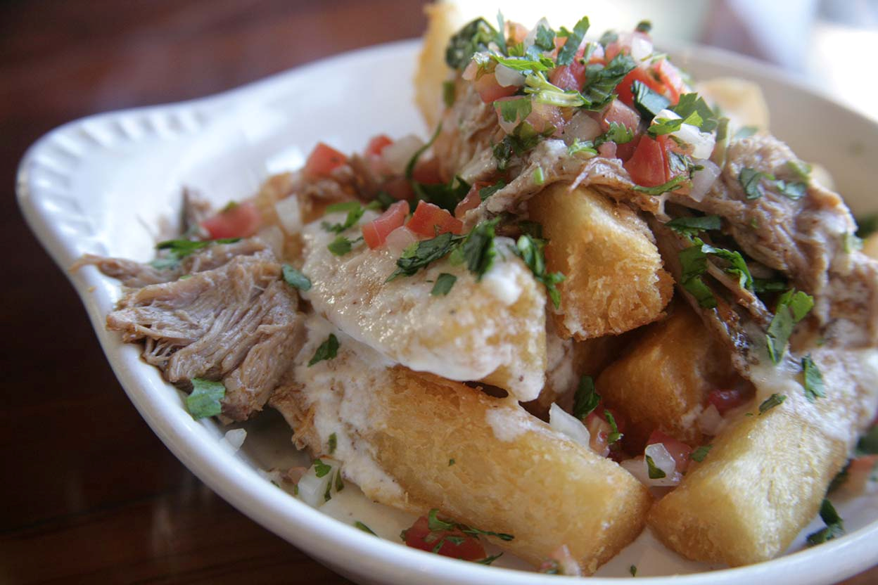 EscaLA's yucca fries are topped with melted cheese, shredded pork and salsa.