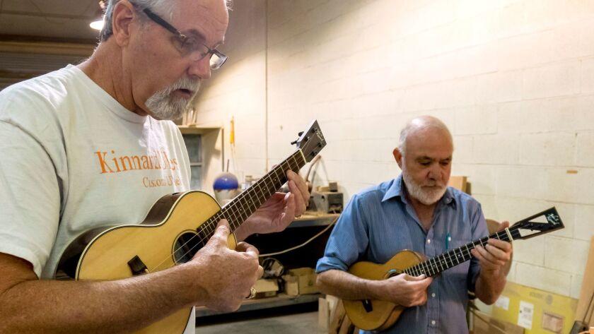 KinnardUkes owner Kevin Beddoe, left, and master ukulele builder John S. Kinnard play some of Kinnard's instruments at his Fallbrook workshop in June 2017.
