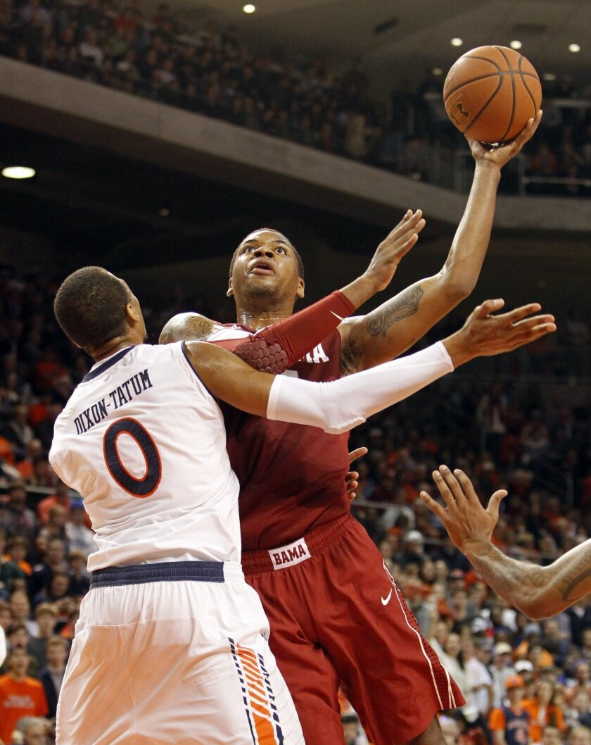 Alabama's Nick Jacobs (15) puts up a shot over Auburn's Asauhn Dixon-Tatum (0) during the first half of an NCAA college basketball game, Thursday, Jan. 30, 2014, in Auburn, Ala. (AP Photo/Butch Dill)