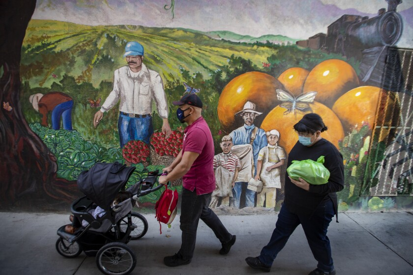 Pedestrians, one pushing a stroller, wear masks as they pass a mural of farmworkers