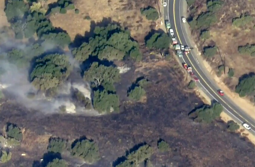 Cars line Santiago Canyon Road near the point of origin of the Silverado fire that started early Monday.