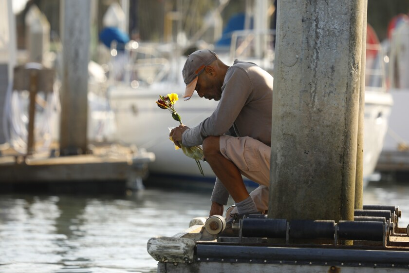 At Santa Barbara Harbor on Monday, James Miranda kneels in prayer for passengers on the Conception.