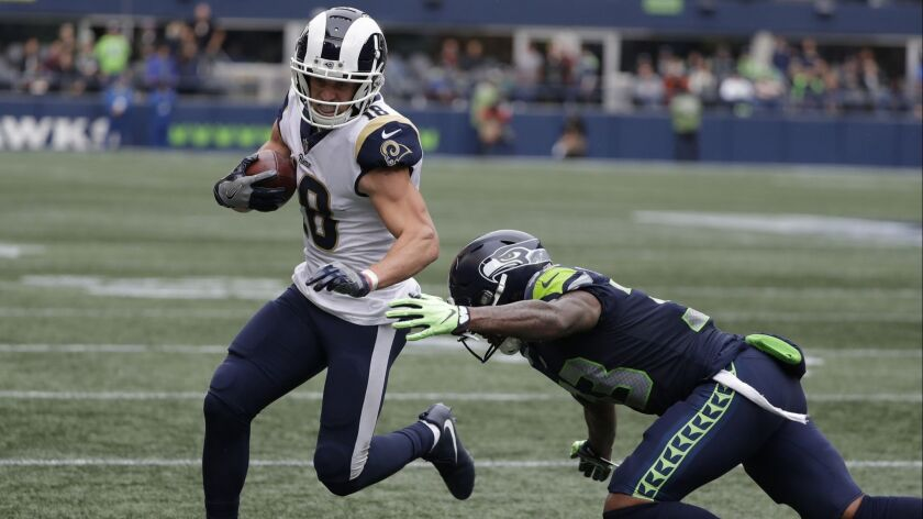 Los Angeles Rams wide receiver Cooper Kupp avoids a tackle by Seattle Seahawks free safety Tedric Th