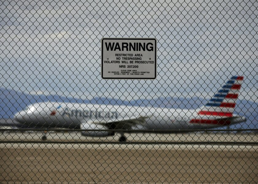 FILE - In this May 17, 2016, file photo, a sign warns against trespassing as a plane lands at McCarran International Airport in Las Vegas. While intruders routinely breach the security fences protecting runways and planes at U.S. airports, the federal Transportation Security Administration is not k