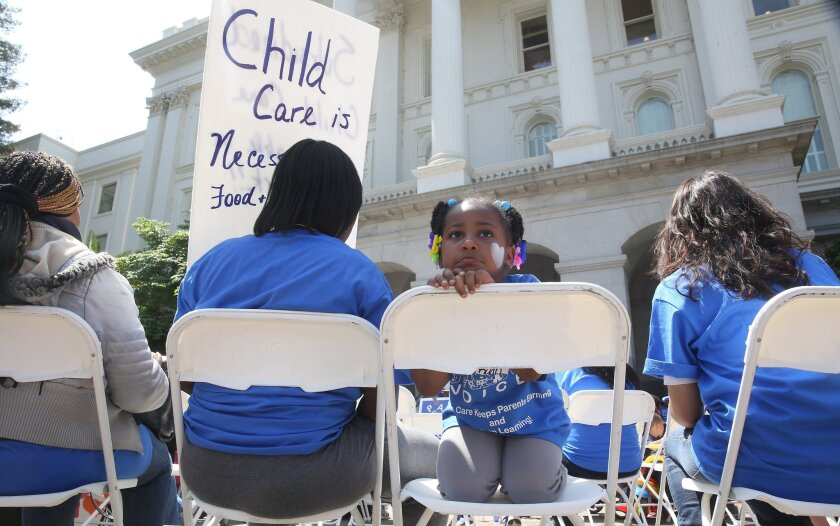 A young girl sits with her mother at a rally calling for increased child care subsidies at the Capitol in Sacramento on May 6.