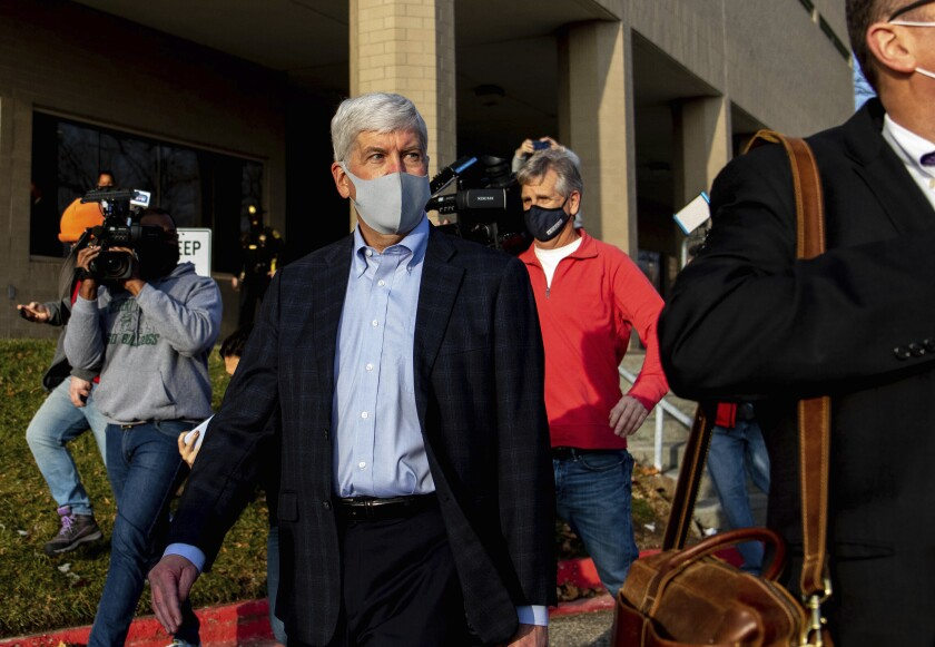 Former Gov. Rick Snyder walks past the media after his video arraignment on charges related to the Flint water crisis on Thursday, Jan. 14, 2021 outside the Genesee County Jail in downtown Flint. Snyder pleaded not guilty to misdemeanor charges of willful neglect of duty in Flint. (Cody Scanlan/The Flint Journal via AP)
