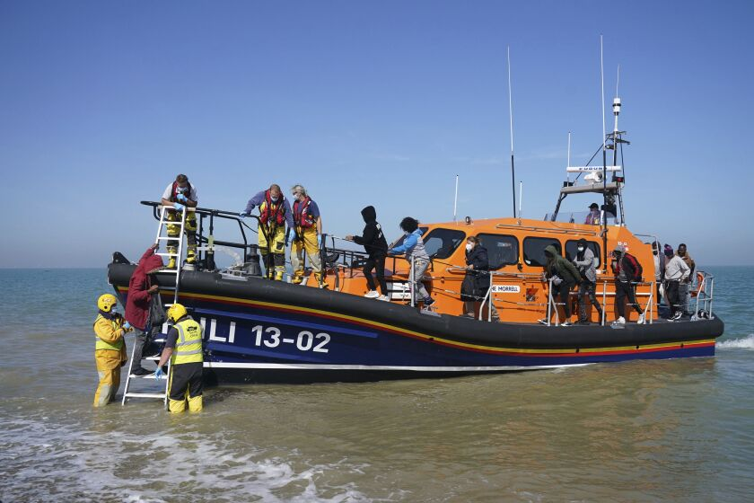 A group of people thought to be migrants are brought ashore from the local lifeboat at Dungeness in Kent, after being picked-up following a small boat incident in the Channel, England, Tuesday, Sept. 7, 2021. (Gareth Fuller/PA via AP)