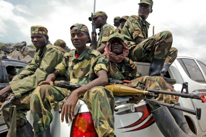 M23 rebel fighters sit in the back of a pickup truck as they prepare to leave the eastern Congolese city of Goma in December.