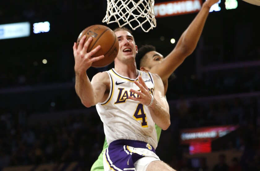 Lakers guard Alex Caruso puts up a shot in front of Minnesota Timberwolves center Karl-Anthony Towns.