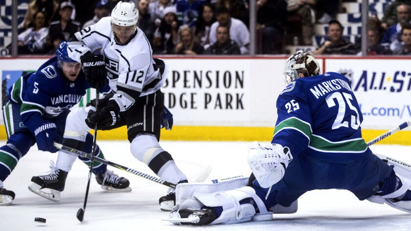 Kings winger Marian Gaborik (12) skates across the crease trying to score against Canucks goalie Jacob Markstrom and defenseman Derrick Pouliot during the third period Saturday.
