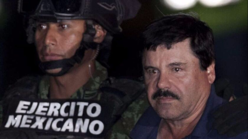 """Mexican drug lord Joaquin """"El Chapo"""" Guzman, right, is escorted by soldiers and marines to a waiting"""