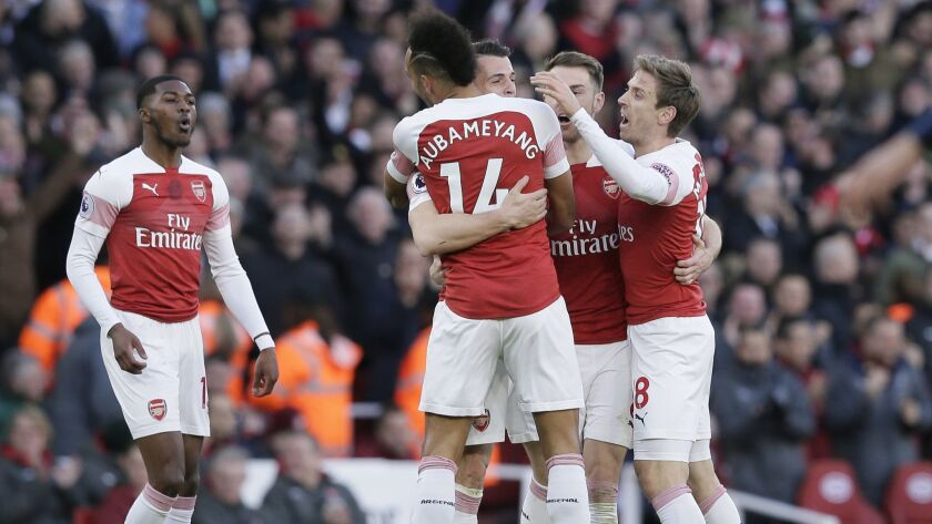Arsenal players celebrate after scoring a goal against Manchester United on March 10.