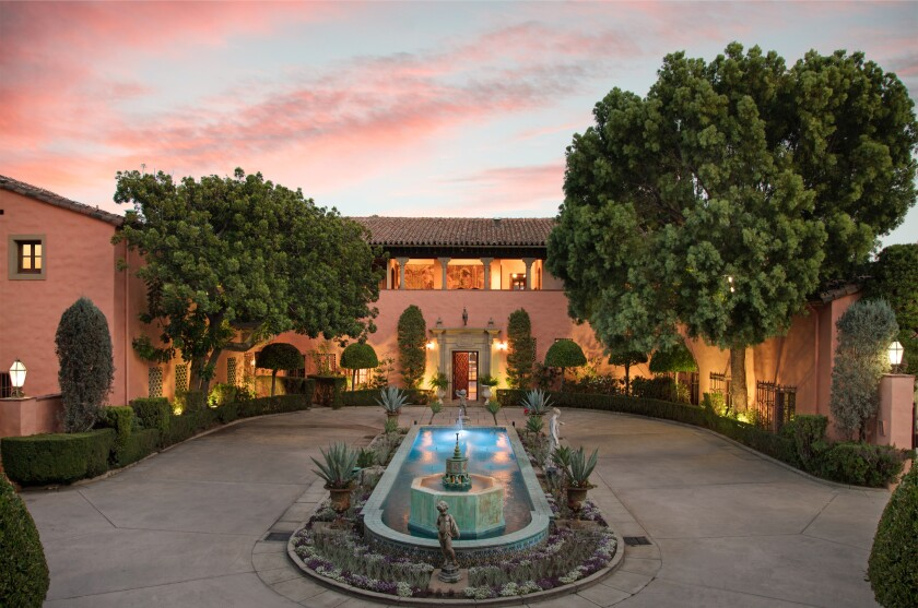 The Mediterranean Revival-style mansion with a fountain in front.