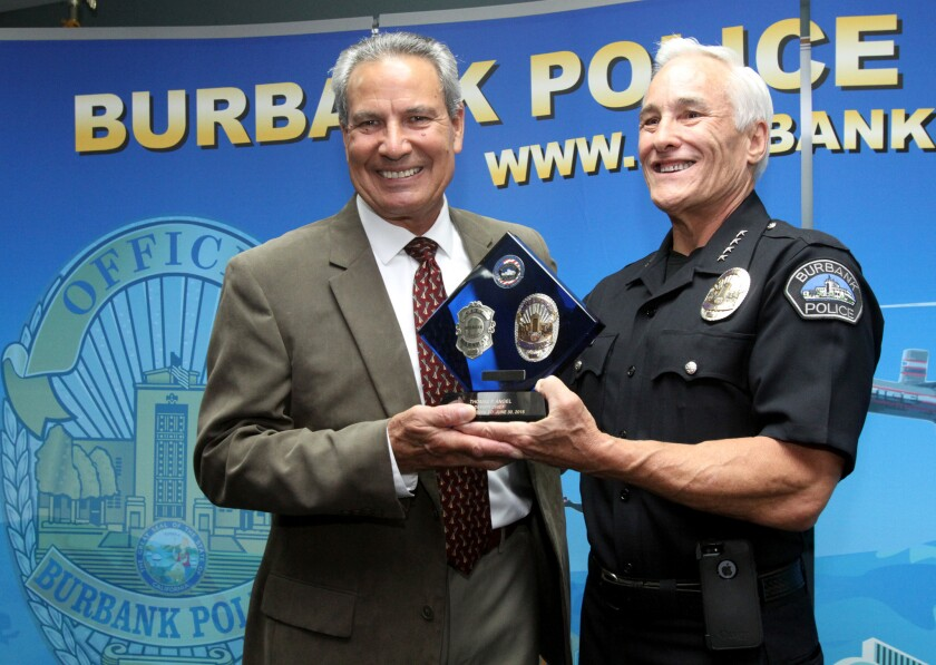 Burbank Police Dept. Deputy Chief Tom Angel, left, is given a plaque by Chief Scott LaChasse during brief retirement ceremony at police headquarters in Burbank on Tuesday, June 23, 2015.