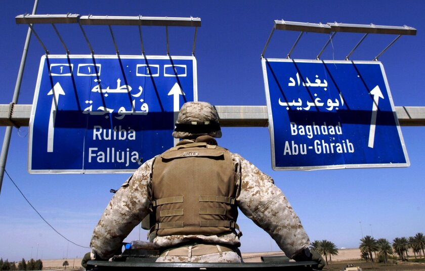 Marine Lance Cpl. Daymond Geer, 21, who is manning machine gun mounted on top of the cab of a 7 ton truck, looks up at highway signs showing the way to Baghdad, Abu-Ghraib, and Fallujah as the 2nd Battalion, 1st Marine Regiment roll up Highway 1 to Fallujah, Iraq on Tuesday, March 16, 2004. The Mar
