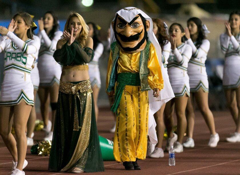 In this Nov. 8, 2013 photo, the Coachella Valley High School Arab mascot, right, is walks the sideline with Coachella's genie mascot during the Victory Bell game at Indio High School, in Indio, Calif. Arab-Americans recently objected to the hook-nosed, snarling image used to represent Coachella Valley High School. The school has agreed to give the mascot a makeover, but not to drop the nickname. (AP Photo./The Desert Sun, Gerry Maceda) RIVERSIDE PRESS-ENTERPRISE OUT; NO SALES