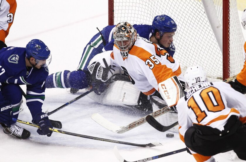 Vancouver Canucks' Jake Virtanen (18) collides with Philadelphia Flyers goaltender Steve Mason during the second period of an NHL hockey game in Vancouver, British Columbia, Monday, Nov. 2, 2015. (Ben Nelms/The Canadian Press via AP) MANDATORY CREDIT