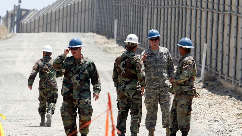 Members of the California National Guard next to the U.S.-Mexico border fence on June 21, 2006.
